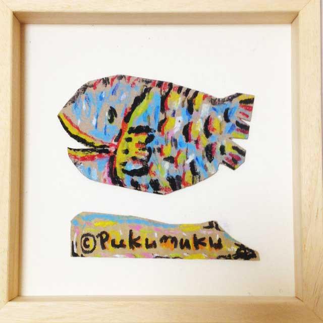 ダンボールにカラフルな魚を描く。額装