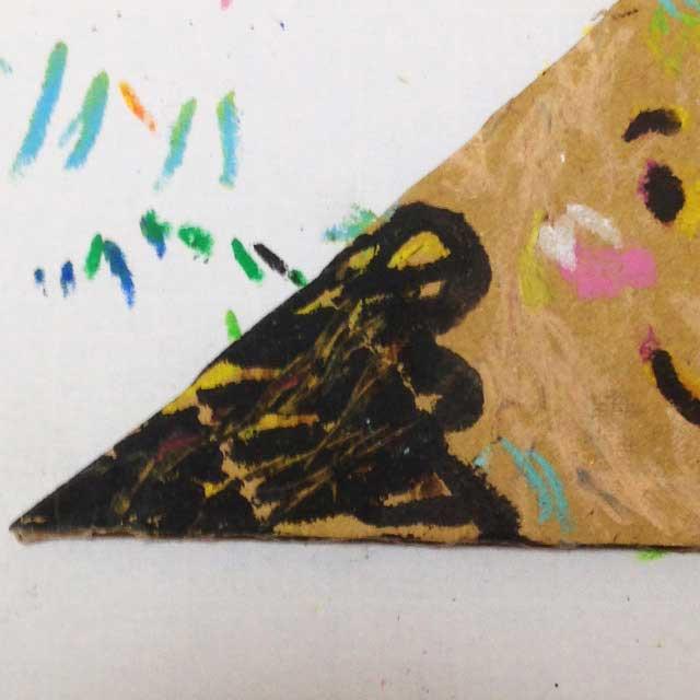 ダンボールに三角の顔を描く。部分アップ