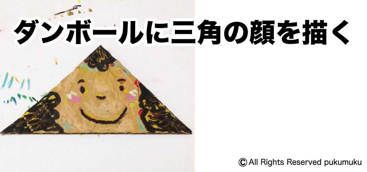 ダンボールに三角の顔を描く
