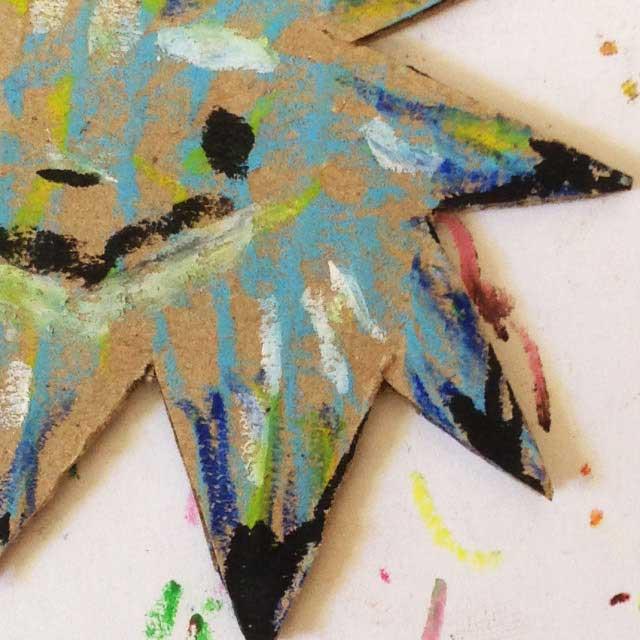 ダンボールに青い星を描く。拡大