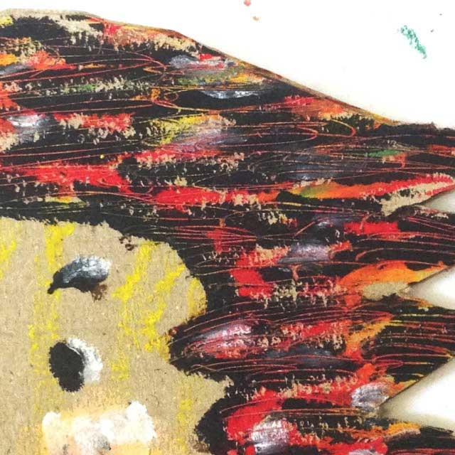 ダンボールに赤髪の人を描く。拡大